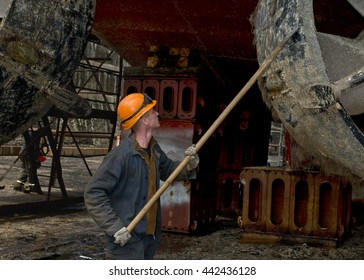 Worker cleans the hull of the ship from the shells and algae
