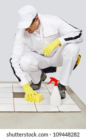 worker cleans with sponge and spray old tiles floor before tiling