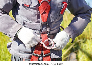 worker climber preparing for steeplejack work. climber tightens the safety belt and check fixing and carbines. closeup