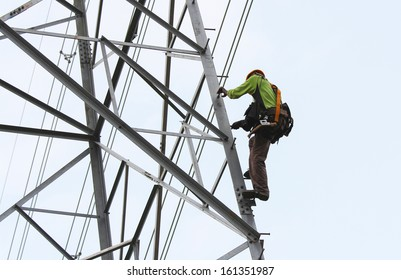 worker climbing on transmission line tower