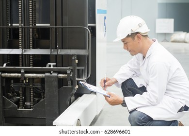 Worker with clipboard checking equipment in warehouse