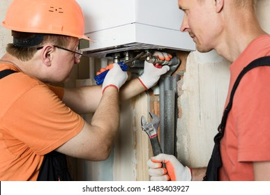 The worker is connecting the pipes to a domestic gas boiler