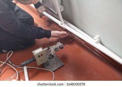 Worker connecting plastic pipe. Installing water heating radiator