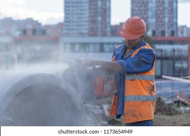 Worker at the construction site cuts the concrete ring for the well with a concrete cutter