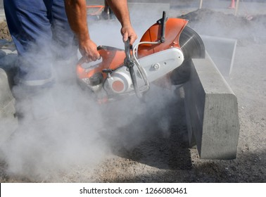 A worker at the construction site cuts the concrete block with a saw.