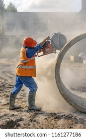 Worker at the construction site cuts the ring for the well with concrete cutters