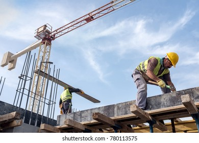 Worker At The Construction Site Is Fixing Forms For The Beams.