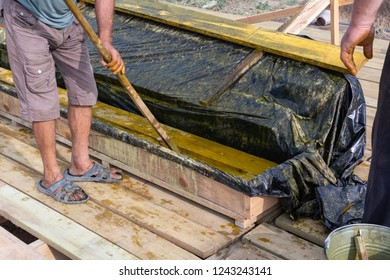 Worker at a construction site at home covers antiseptic boards. Impregnation of boards.