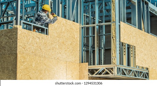 Worker and Construction Site. Skeleton Steel Frame Installation.