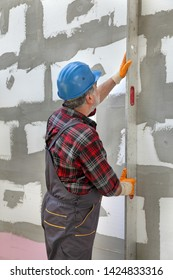 Worker control styrofoam, polystyrene  insulation of wall with level tool