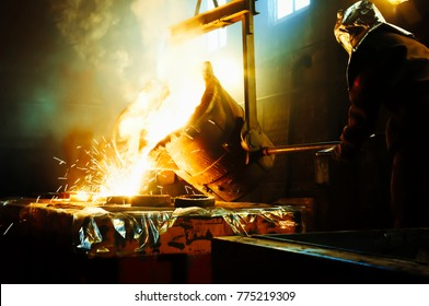 Worker controlling metal melting in furnaces. Man operates at the metallurgical plant. The liquid metal is poured into molds.