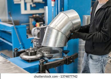 Worker controls the machine. Production rolling tool, electric machine. the production of ventilation and gutters. Tool and bending equipment for sheet metal.