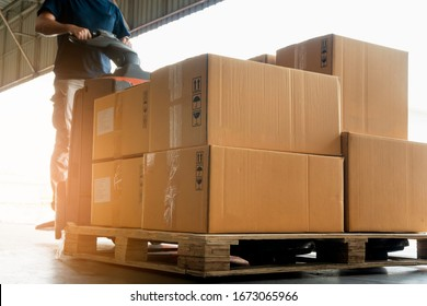 Worker courier is driving electric forklift pallet jack loading shipment goods, package boxes, warehouse delivery service shipment and transport.