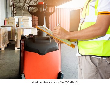 Worker courier holding clipboard inspecting checklist load shipment goods into a truck, Freight industry warehouse logistics transport, Electric forklift pallet jack loading shipment goods.