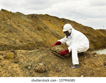 worker in coveralls and mask takes a sample of the soil in the contaminated area
