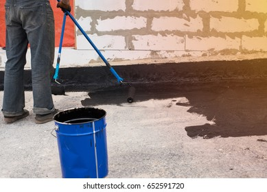 Worker covered surface, bitumen primer for improving adhesion during surfacing,  rolled waterproofing, during the installation of isolation on industrial or household objects Copy  space