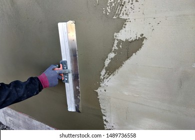 Worker covering insulated wall with solution of glue over plastered styrofoam insulation.