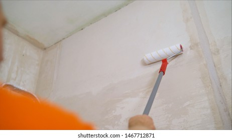 A worker covers the wall with plaster. Worker and roller. Male hand painting wall with paint roller. Painting apartment, renovating with white color paint