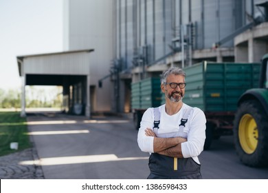 worker crossed arms standing in front of grain silo