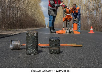 Worker cut by the core sampler samples of asphalt concrete on the road. Asphalt concrete cores close-up