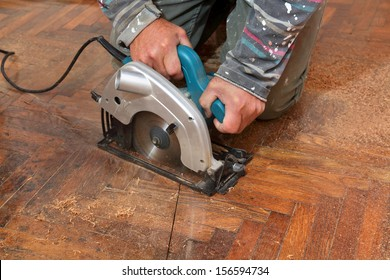 Worker cut old parquet floor with electric saw