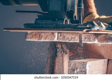 The worker cuts boards with an electric jigsaw, dust flies in all directions, carpentry