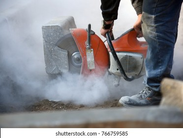 A worker cuts concrete curb circular saw at a construction site