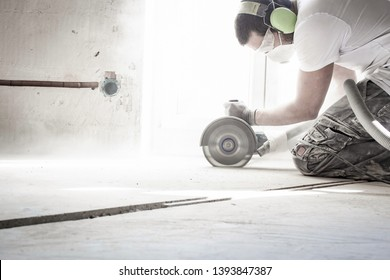 worker cuts concrete floor with electrical flex
