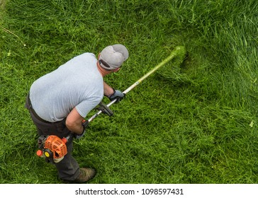 A worker cuts grass in Montreal on Friday, May 25, 2018.
