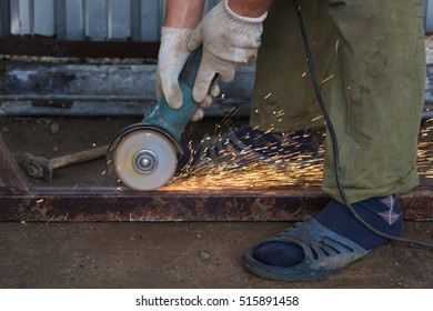 Worker cuts metal profile with the angle grinder machine, grinder