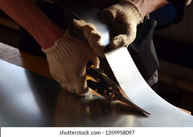 worker cuts a stainless sheet with scissors for metal
