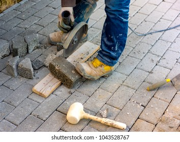Worker cuts a tile to size with an electric grinder to complete the self-locking paving