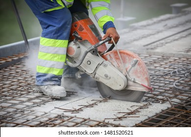 Worker is cutting concrete with circular saw for concrete, detail of the construction scene.