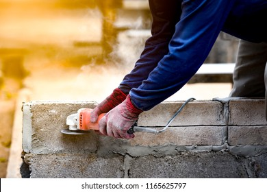 Worker cutting concrete concept, cutting concrete machine on brick block wall by workman in industry site of building structure. He wearing glove for protect and safety for working in this site