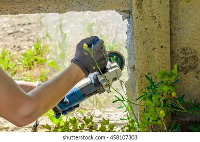 worker cutting a  concrete fence using an angle grinder at construction site