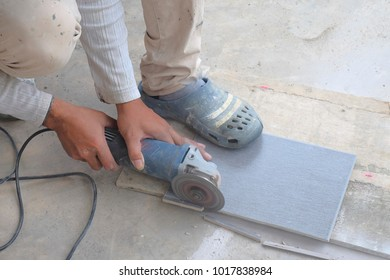 Worker cutting floor tiles with angle grinder  at construction site. Kitchen renovation  and improvement.