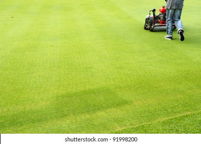 worker cutting grass on golf green. .Lawn mower cutting green grass in backyard,Garden service,grass cutter cutting green lawns.