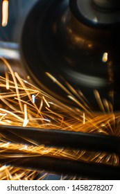 Worker cutting, grinding and polishing motorcycle metal part with sparks indoor workshop. Super macro close-up. Vertical