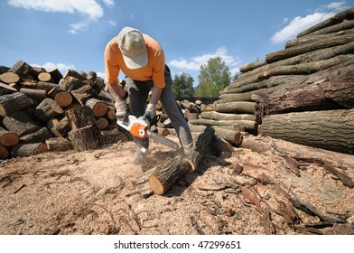 Worker cutting logs with a chainsaw