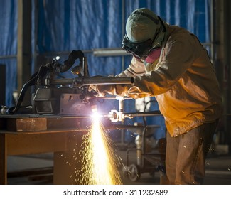 Worker cutting metal with acetylene torch close-up on low ligth