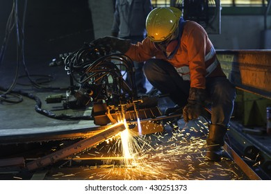 Worker cutting metal with acetylene torch at construction site