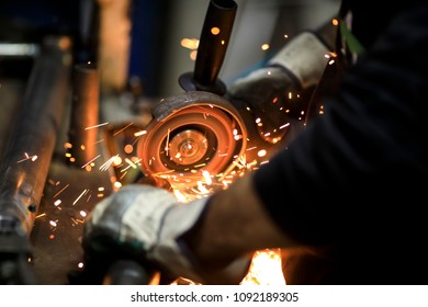 Worker cutting metal with grinder in factory