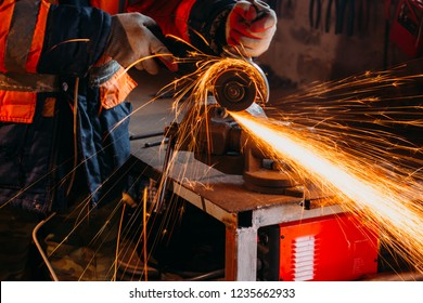 Worker cutting metal with grinder in his workshop. Sparks while grinding iron
