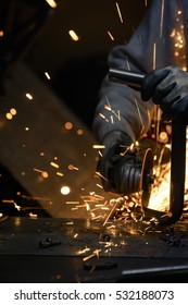 Worker cutting metal with grinder. Sparks flying while grinding steel pipe. Vertical photo.