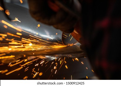 Worker cutting metal part using hand Angle Grinder Machine. Freeze motion sparks , close-up.