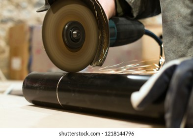 A worker cutting of a metal pipe with an angle grinder