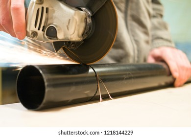 A worker cutting of a metal pipe with a power tool angle grinder