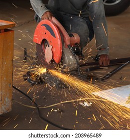 Worker cutting metal and spark with cutting machine