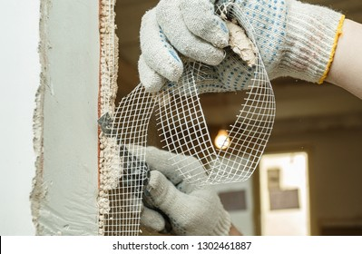 A worker is cutting off a piece of fiberglass mesh with a knife during an apartment renovation