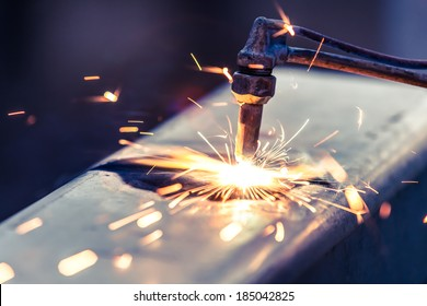 worker cutting steel pipe using metal torch and install roadside fence